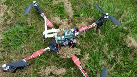 A quadcopter fitted with a Raspberry Pi, sat on grass